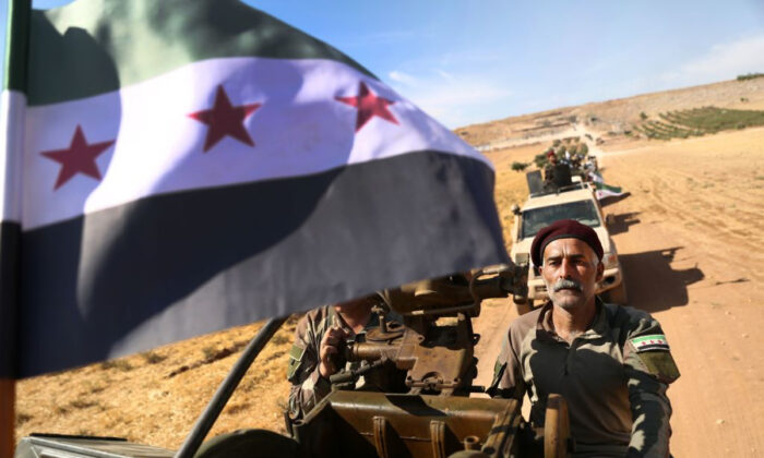 """Turkish-backed Syrian rebel fighters head to an area near the Syrian-Turkish border north of Aleppo on October 8, 2019. The Kurdish-led Syrian Democratic Forces said in a statement that """"US forces withdrew from the border areas with Turkey"""" in northeast Syria. (Nazeer Al-Khatib/AFP via Getty Images)"""