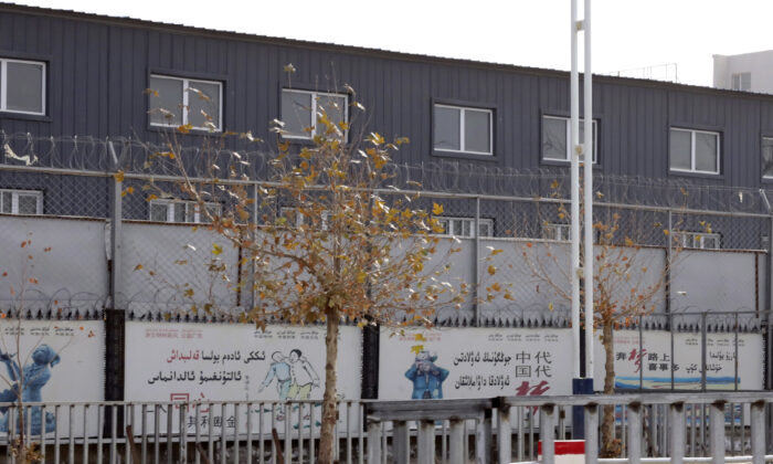 """Two layers of barbed wire fencing ring the """"Hotan City apparel employment training base"""" where Hetian Taida Apparel Co. has a factory in Hotan in western China's Xinjiang region, on Dec. 5, 2018. The Trump Administration is blocking shipments from Chinese company Hetian Taida Apparel, which makes baby pajamas sold at Costco warehouses, after the foreign manufacturer was accused of forcing ethnic minorities locked in an internment camp to sew clothes against their will. (Ng Han Guan/AP)"""