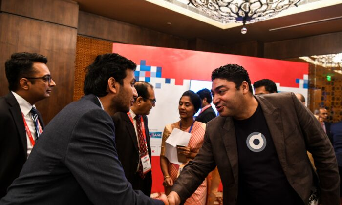 CEO and co-founder of Poynt Osama Bedier (R) and Indian entrepreneur and founder of Oyo Rooms Ritesh Agarwal (L) meet backstage at the ET Global Business Summit in New Delhi on Feb. 23, 2019. (Chandan Khanna/AFP/Getty Images)