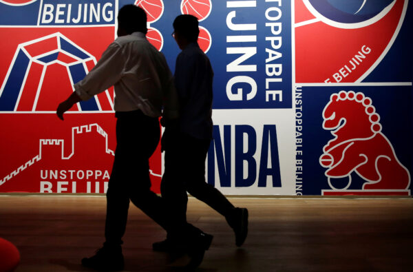 Men walk past a poster at an NBA exhibition in Beijing