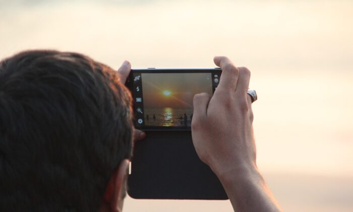 In this file image, a man takes a photograph of the sunset with his phone. (Pixabay)