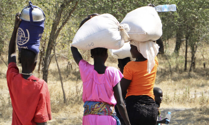 In this Friday, Dec. 7, 2018 file photo, women and girls walk back after getting food in Bentiu, a 38 kilometers (24 miles) journey using a path through the bush, for fear of being attacked on the main road, near Nhialdu in South Sudan on Oct. 7, 2019. (AP Photo/Sam Mednick, File)