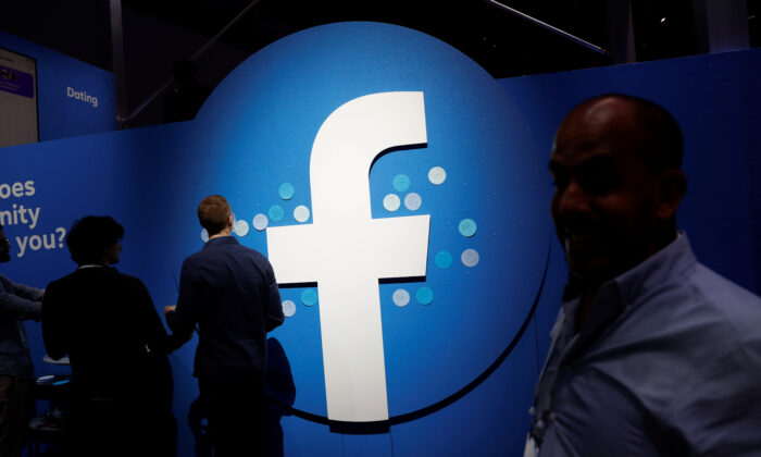 Attendees walk past a Facebook logo during Facebook's F8 developers conference in San Jose, Calif., on April 30, 2019. (Stephen Lam/Reuters)