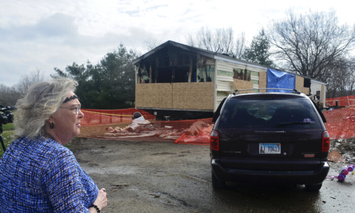 Marie Chockley, a resident of the Timberline Trailer Court, north of Goodfield, Ill., surveys the damage that was caused by a Saturday night fire that killed five residents in a mobile home on April 7, 2019. (Kevin Barlow/The Pantagraph via AP)