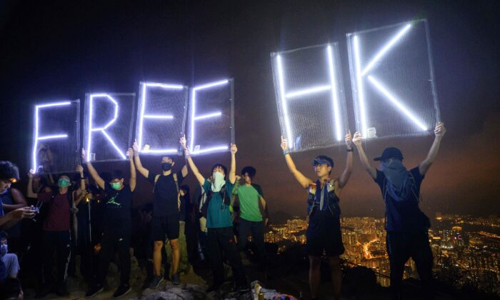 "Pro-democracy activists hold up LED lit letters which read ""Free HK"" while forming a human chain on Lion Rock in Hong Kong on Sept. 13, 2019. An NBA fan in America said he was ejected for shouting ""Free Hong Kong"" on Oct. 8, 2019. (Anthony Wallace/AFP via Getty Images)"