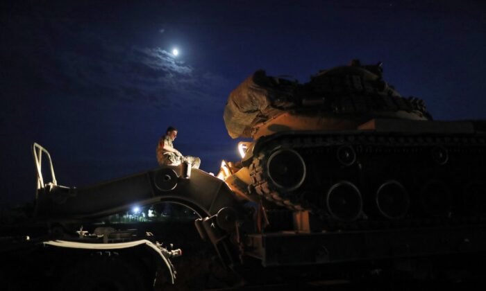 A Turkish army officer prepares to upload a tank from a truck to its new position on the Turkish side of the border between Turkey and Syria, in Sanliurfa province, southeastern Turkey, on Oct. 8, 2019. (Lefteris Pitarakis/AP Photo)