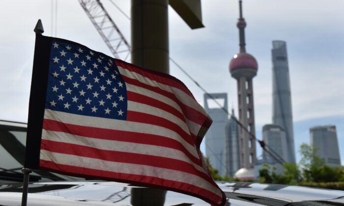 A U.S. flag flies on a U.S. consulate car with the backdrop of buildings in the Lujiazui financial district, outside a hotel where U.S. trade negotiators are staying in Shanghai, China on July 31, 2019. (Greg Baker/AFP/Getty Images)