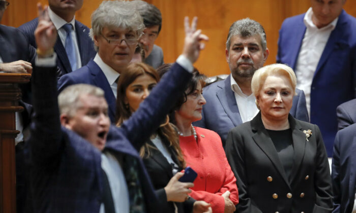 Romanian Prime Minister Viorica Dancila (R) watches as an opposition lawmaker flashes victory signs after casting his vote during a no confidence vote in Bucharest, Romania on Oct. 10, 2019. (Vadim Ghirda/AP Photo)
