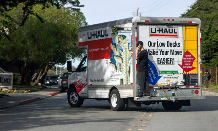 A man talks on his cell phone while riding on the back of a moving truck in Pacifica, Calif., on Jan. 26, 2016. (Josh Edelson/AFP/Getty Images)