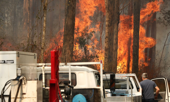 Local residents are seen near a bushfire burning next to Busby's Flat Road in Busbys Flat, northern NSW, Wednesday, Oct. 9, 2019. (AAP Image/Jason O'Brien)