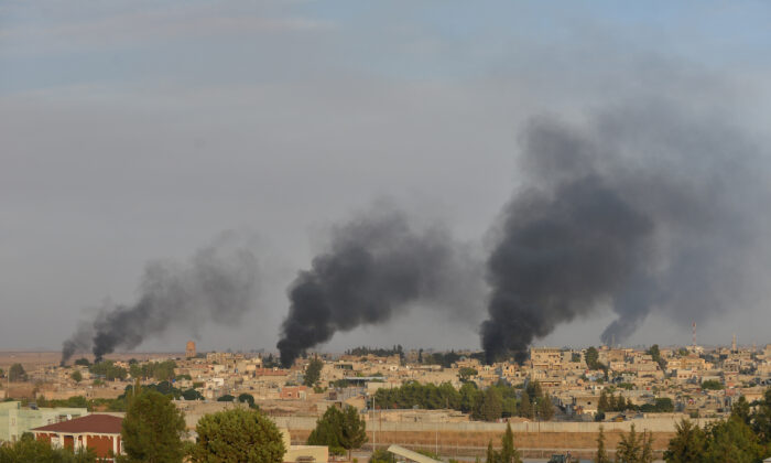 Smoke rises from the Syrian border town of Ras al-Ain as it is pictured from the Turkish town of Ceylanpinar in Sanliurfa province, Turkey, Oct. 9, 2019.  (Reuters/Stringer)