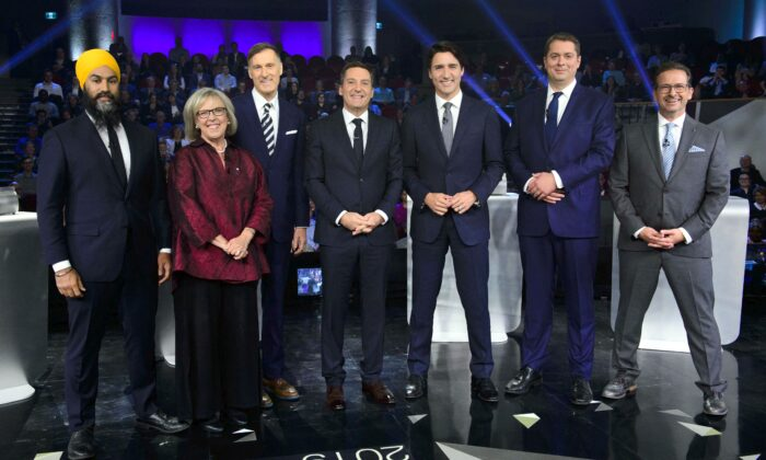 Host Patrice Roy from Radio-Canada (C) with federal party leaders (L-R) NDP Leader Jagmeet Singh, Green Party Leader Elizabeth May, People's Party Leader Maxime Bernier, Liberal Leader Justin Trudeau, Conservative Leader Andrew Scheer, and Bloc Quebecois Leader Yves-Francois Blanchet before the Federal leaders French-language debate in Gatineau, Que., on Oct. 10, 2019. (THE CANADIAN PRESS/Sean Kilpatrick)