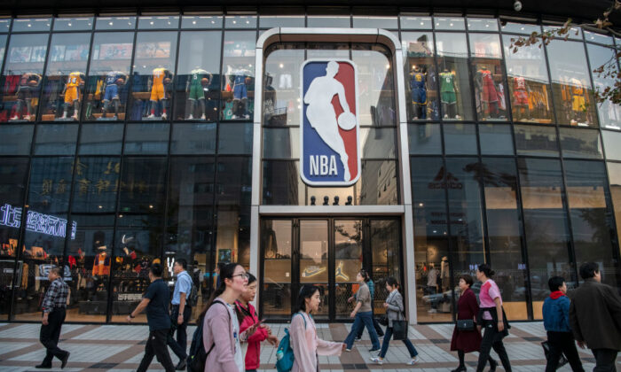 People walk by the NBA flagship retail store on October 9, 2019 in Beijing, China.  Kevin Frayer/Getty Images