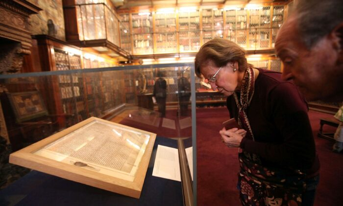 Visitors look at one of the earliest original manuscripts of the Magna Carta from 1217 at the Morgan Library & Museum on April 21, 2010, in New York City. (Mario Tama/Getty Images)