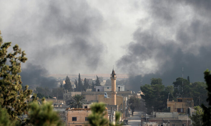 Smoke rises over the Syrian town of Tel Abyad, as seen from the Turkish border town of Akcakale in Sanliurfa province, Turkey, on Oct. 10, 2019. (Murad Sezer/Reuters)