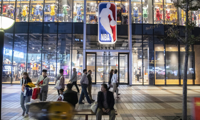 People walk by and sit outside the NBA flagship retail store on Oct. 9, 2019 in Beijing, China. (Kevin Frayer/Getty Images)