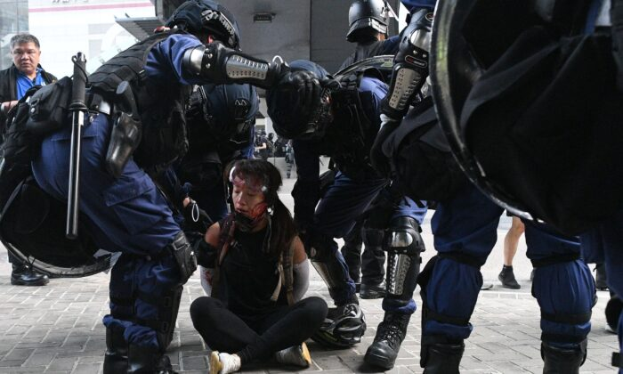 Hong Kong police detain a woman (on ground) near the central government offices after thousands took part in an unsanctioned march through Hong Kong on Sept. 29, 2019. (Mohd Rasfan/AFP via Getty Images)