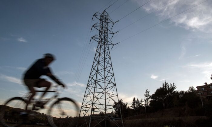 A bicyclist rides passed high-tension power lines in Mill Valley, California as a statewide blackout continues on Oct., 10, 2019. (Josh Edelson/AFP via Getty Images)