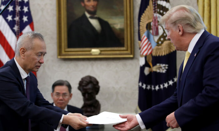 "Chinese Vice Premier Liu He presents U.S. President Donald Trump with a letter from Chinese leader Xi Jinping after Trump announced a ""phase one"" trade agreement was reached with China in the Oval Office at the White House in Washington, DC on October 11, 2019. (Photo by Win McNamee/Getty Images)"