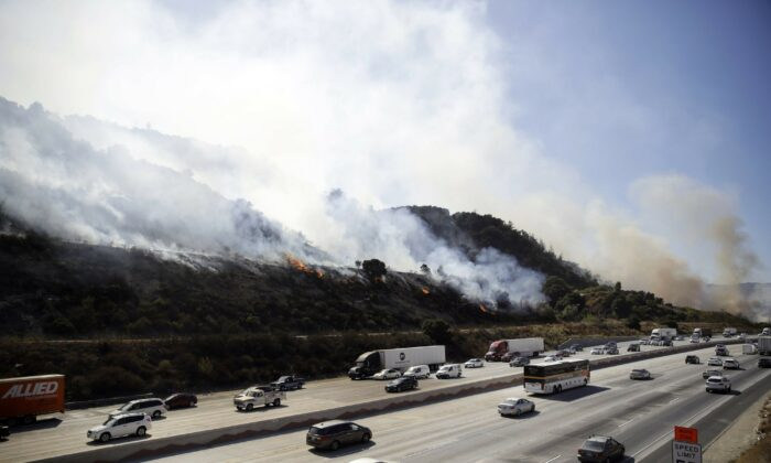 Smoke from a wildfire engulfs a hillside as traffic flows along I-5 Freeway in Newhall, Calif., on Oct. 12, 2019. (Marcio Jose Sanchez/AP Photo)