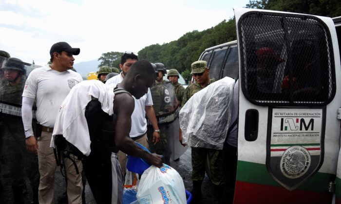 Agents of the National Migration Institute (INM) detain migrants from a caravan of migrants from Africa, the Caribbean and Central America, hours after they embarked toward the United States, in Tuzantan, Mexico, on Oct. 12, 2019. (Jacob Garcia/Reuters)
