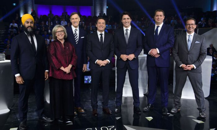 Host Patrice Roy from Radio-Canada (C) with federal party leaders (L-R) NDP Leader Jagmeet Singh, Green Party Leader Elizabeth May, People's Party Leader Maxime Bernier, Liberal Leader Justin Trudeau, Conservative Leader Andrew Scheer, and Bloc Quebecois Leader Yves-Francois Blanchet before the leaders' French-language debate in Gatineau, Que., on Oct. 10, 2019. (THE CANADIAN PRESS/Sean Kilpatrick)