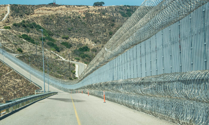"""The secondary fence of the U.S.-Mexico border is near an area popularly known as """"Smuggler's Gulch,"""" in San Diego on July 12, 2017. The Border Patrol added a second layer of concertina wire along the bottom of the fence which helped curtail assaults on agents. (Joshua Philipp/The Epoch Times)"""