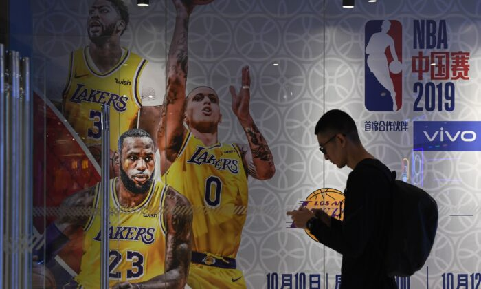 A man walks past an advertisement for scheduled exhibition games in China between the LA Lakers and Brooklyn Nets, at the National Basketball Association (NBA) store in Beijing on Oct. 9, 2019. (Greg Baker/AFP via Getty Images)