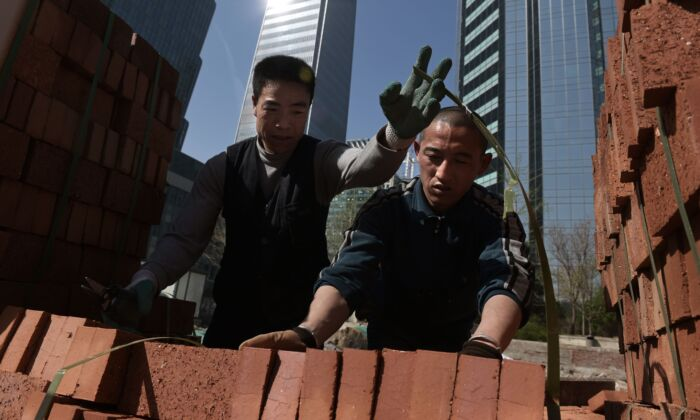 Workers handle bricks to build a wall in Beijing on March 27, 2019. (NICOLAS ASFOURI/AFP/Getty Images)