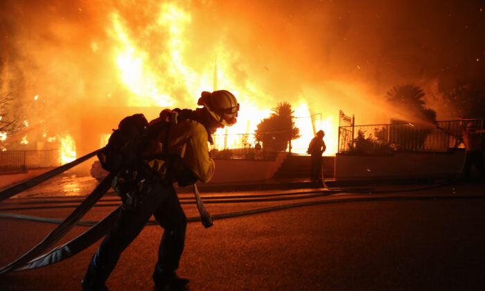 Firefighters work at a house fire in the early morning hours during the Saddleridge Fire on Oct. 11, 2019 in Porter Ranch, Calif. (Mario Tama/Getty Images)