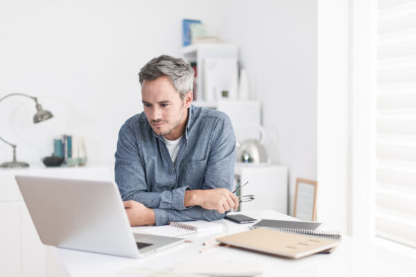 man is sitting at a white table looking at his laptop