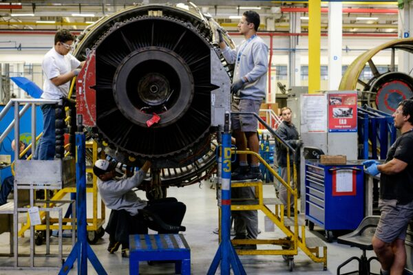 Men work with a jet engine at a General Electric (GE) aviation engine overhaul facility in Petropolis, Rio de Janeiro, Brazil