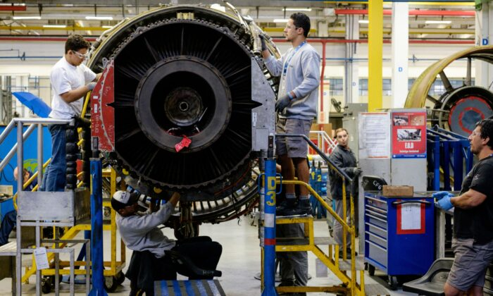 Men work with a jet engine at a General Electric (GE) aviation engine overhaul facility in Petropolis, Rio de Janeiro, Brazil on June 8, 2016. (Yasuyoshi Chiba/AFP/Getty Images)