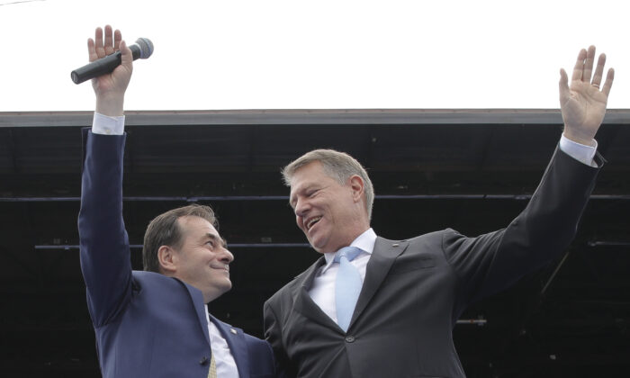 Liberal party President Ludovic Orban (L) and Romanian President Klaus Iohannis wave on stage during an European Parliament electoral rally in Bucharest, Romania on May 18, 2019. (Vadim Ghirda/AP Photo, File photo)