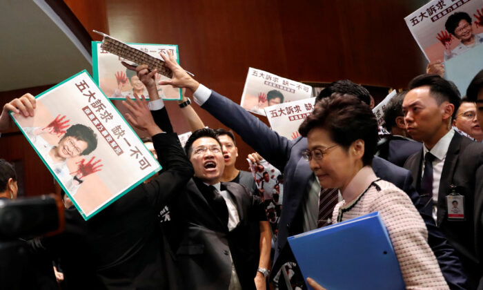 Hong Kong Chief Executive Carrie Lam arrives to deliver her annual policy address, as lawmakers shout protests, at the Legislative Council in Hong Kong, China, on Oct. 16, 2019. (Tyrone Siu/Reuters)