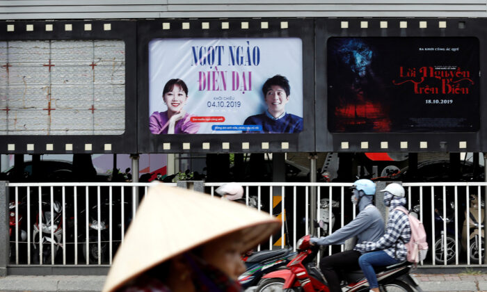 "Bikers go past an empty space where a promotional poster for the DreamWorks film ""Abominable"" stood before being taken down at a cinema in Hanoi, Vietnam on Oct. 14, 2019. (Kham/Reuters)"