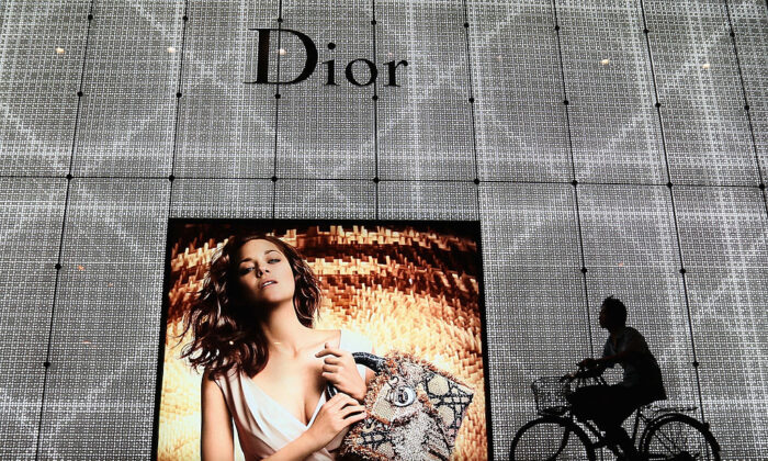 A Chinese man rides a bicycle past an advertisement for the Christian Dior store in Beijing on June 8, 2012. (Feng Li/Getty Images)