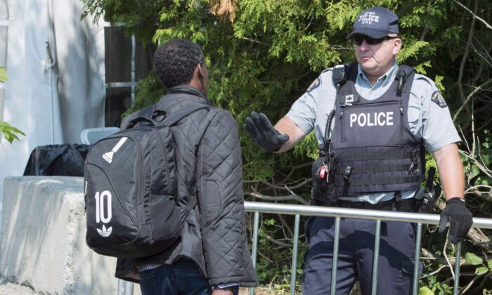 An asylum seeker is questioned by an RCMP officer as he crosses the border unofficially into Canada from the United States near Champlain, New York, on Aug. 21, 2017. (THE CANADIAN PRESS/Paul Chiasson)