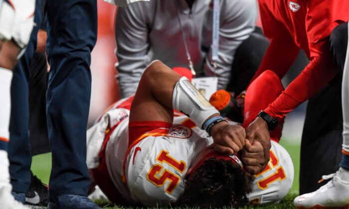 Patrick Mahomes #15 of the Kansas City Chiefs is tended to by trainers after sustaining an injury in the second quarter of a game against the Denver Broncos at Empower Field at Mile High in Denver, Colo., on Oct. 17, 2019. (Dustin Bradford/Getty Images)