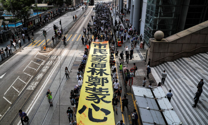 People march with a banner to protest against what they say is the abuse of pro-democracy protesters by Hong Kong police, near Chater Garden in Central district, Hong Kong, China on Oct. 18, 2019. (Ammar Awad/Reuters)