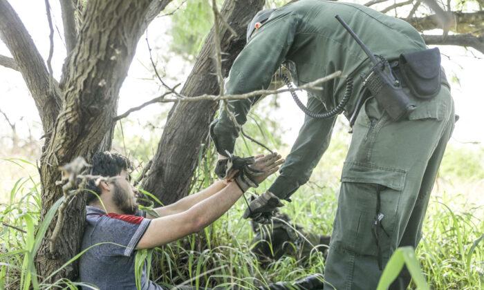 A Border Patrol agent take an illegal alien into custody near McAllen, Texas, on April 18, 2019. (Charlotte Cuthbertson/The Epoch Times)