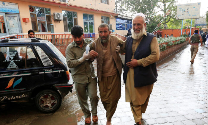 Men carry an injured person to a hospital after a bomb blast at a mosque, in Jalalabad, Afghanistan Oct. 18, 2019. (Parwiz/Reuters)