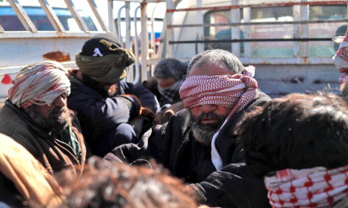 Alleged ISIS fighters who fled from the frontline Syrian village of Baghuz, near the Iraqi border, sit blindfolded in the back of a pickup truck after being taken into custody by SDF forces for screening, near the Omar oil field in the countryside of the eastern Syrian Deir ez-Zor province on Jan. 30, 2019. (Delil Souleiman/AFP/Getty Images)