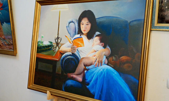 "Painting of a woman holding a child and reading a copy of the book ""Zhuan Falun"" from the Art of Zhen Shan Ren exhibition. (Screenshot/NTD)"