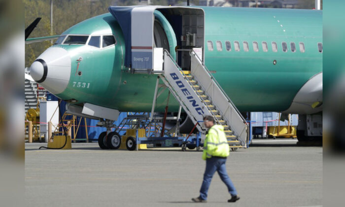 A worker walks past a Boeing 737 MAX 8 airplane being built for Oman Air at Boeing's assembly facility in Renton, Washington on April 26, 2019. (Ted S. Warren/AP Photo, File)
