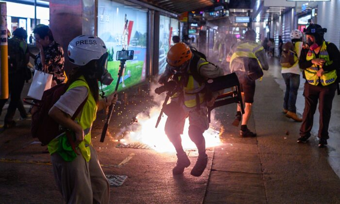 Journalists react as police fire tear gas from Causeway Bay MTR station during clashes with pro-democracy demonstrators in Hong Kong on Sept. 8, 2019. (Philip Fong/AFP/Getty Images)