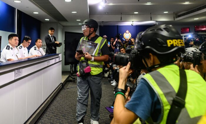 Journalists wear protective gear and high visibility vests at a press conference at police headquarters in Hong Kong on Sept. 9, 2019. (Philip Fong/AFP/Getty Images)