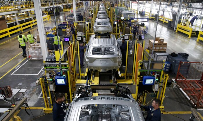 Workers assemble cars at the newly renovated Ford assembly plant in Chicago on June 24, 2019.  (JIM YOUNG/AFP/Getty Images)