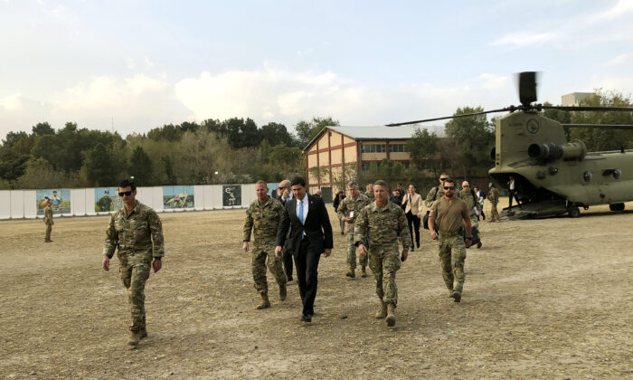 Defense Secretary Mark Esper, center, walks Gen. Scott Miller, right, chief of the U.S.-led coalition in Afghanistan, at the U.S. military headquarters in Kabul, Afghanistan on Oct. 20, 2019. (AP Photo/Lolita C. Balbor)