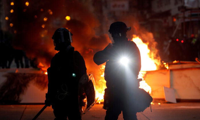 Police officers stand next to a burning barricade during a pro-democracy protest in Hong Kong, China on Oct. 20, 2019. (Ammar Awad/Reuters)